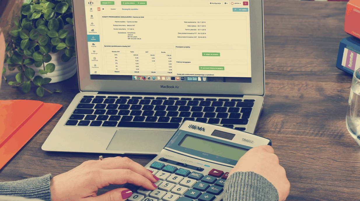 laptop and calculator in a woman's hand